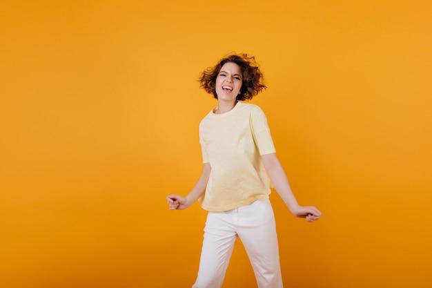 感情的にポーズをとる黄色のtシャツの魅力的な若い女の子。白いズボンで踊り、変な顔を作るファッショナブルな白人の女の子の屋内の肖像画。