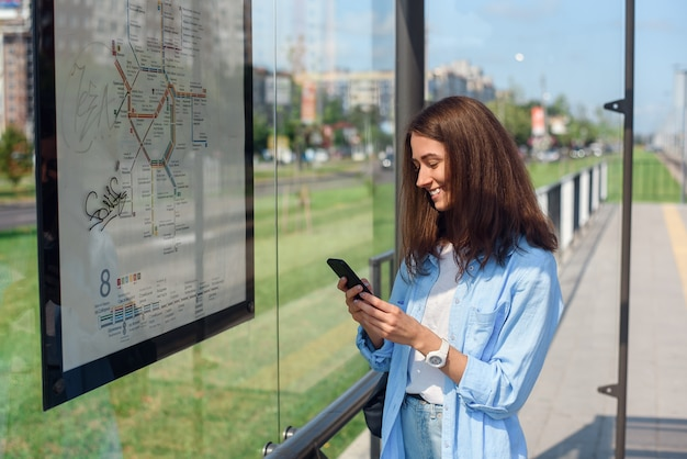 Charming young girl is monitoring the bus through a mobile app while standing at a public transport stop in the morning.