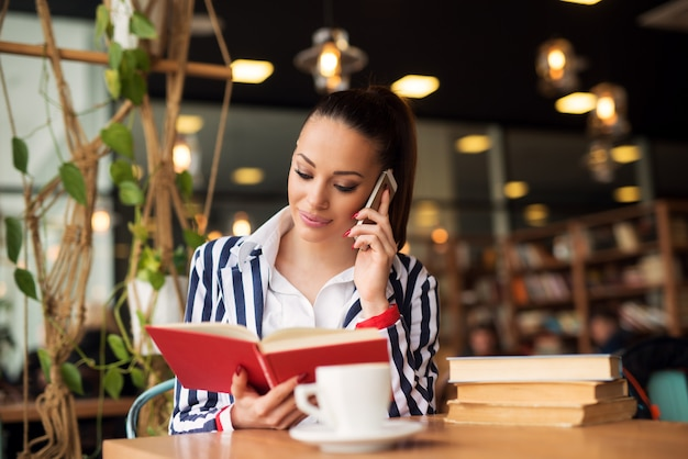 魅力的な若い女の子が本を持っている間携帯電話で話しています。