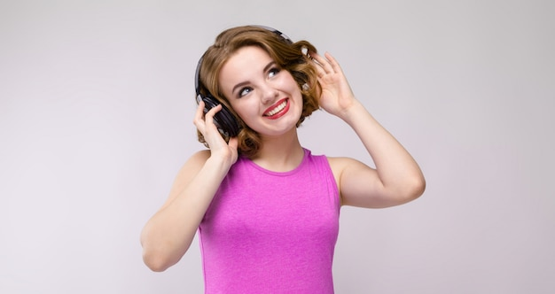 Charming young girl in pink dress on gray background. young girl with headphones smiling