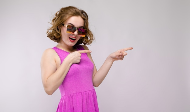 Charming young girl in pink dress on gray  cheerful girl in square glasses the girl points with her fingers to the side