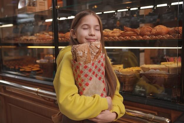 베이커리 스토어에서 갓 구운 빵 냄새가 나는 매력적인 어린 소녀