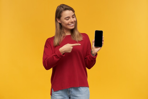 Charming young girl smiles, keeps mobile phone in her hand, black screen turned to the camera, looks on it and points with index finger