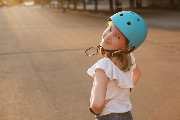 Charming young girl smiling to the camera over her shoulder, wearing protective helmet outdoors, copy space