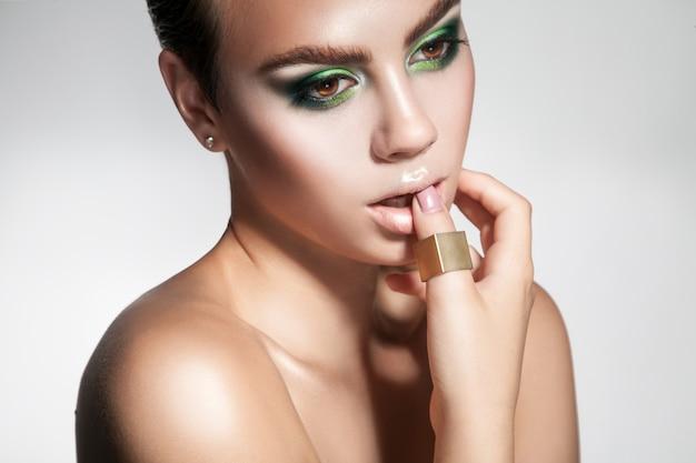 目をそらしている完璧なメイクの魅力的な若い女の子スタジオショット灰色の背景