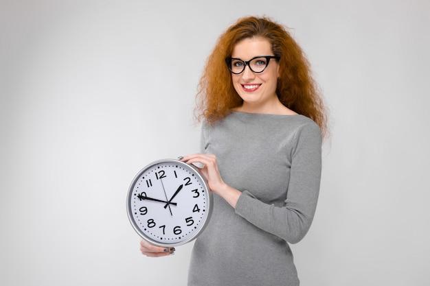 Очаровательная молодая девушка с рыжими волосами. молодая девушка в сером свитере держит часы