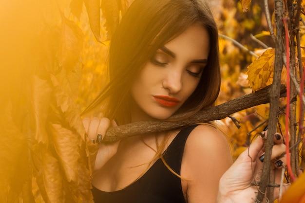 Очаровательная молодая девушка с красными губами и закрытыми глазами позирует в осеннем лесу