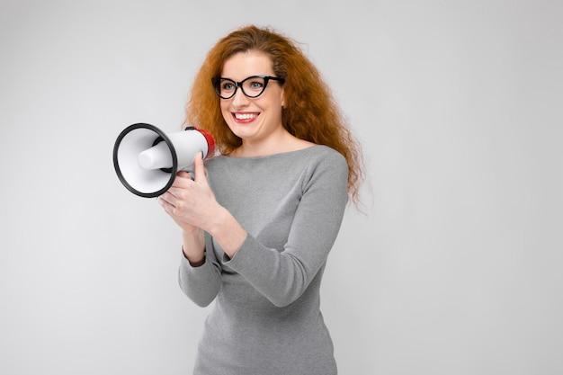 Очаровательная молодая девушка с мегафоном
