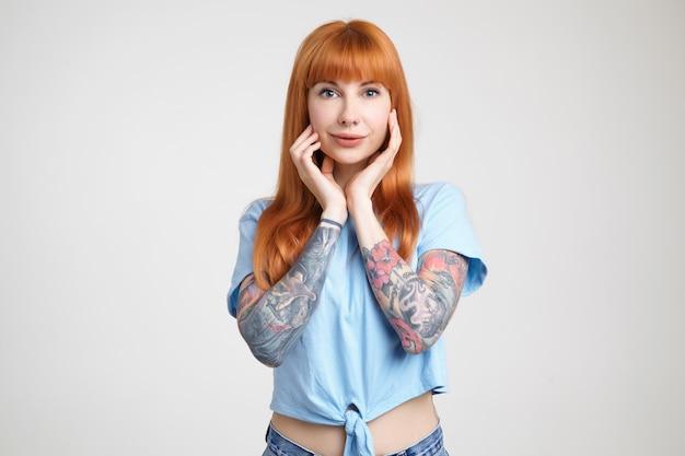 Affascinante giovane signora tatuata dai capelli lunghi dagli occhi verdi che sorride delicatamente mentre guarda positivamente la fotocamera e mantenendo le mani alzate sul viso, isolato su sfondo bianco