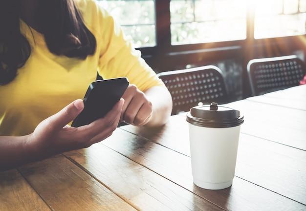 매력적인 젊은 hipster 여자 손 커피 숍에서 나무 테이블에 앉아 그녀의 스마트 폰을 사용 하여. 아시아 여자는 카페-빈티지 컬러 스타일에 앉아 휴식을 취하십시오.