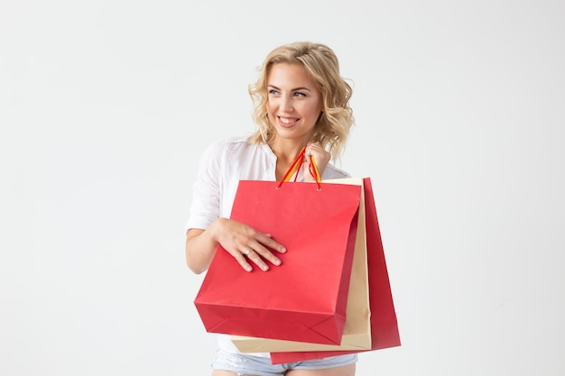 Charming young joyful blonde woman holds in her hands bags with a new clothing posing on a white