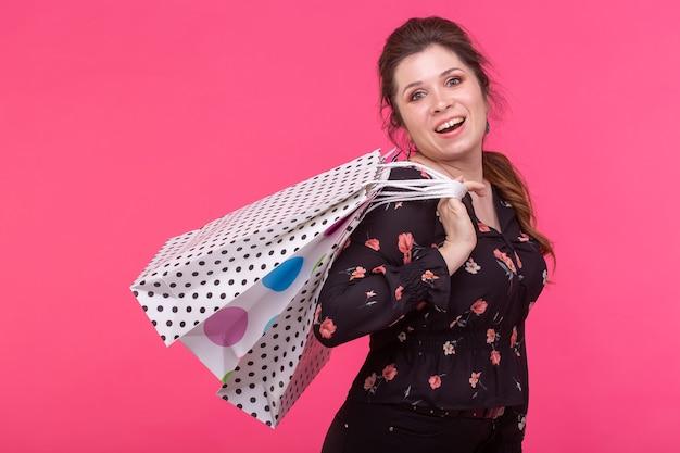 Очаровательная молодая радостная женщина держит в руках сумки с новой одеждой, позируя на розовой поверхности