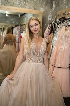 Charming young lady has chosen the perfect evening dress in a clothing store and poses in it. shopping concept