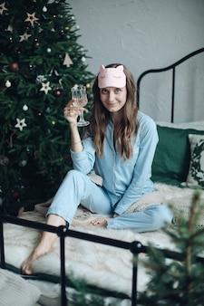 Очаровательная барышня в пижаме радуется с бокалом шампанского во время празднования нового года в своей уютной постели