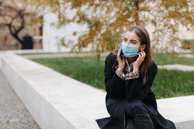 保護フェイスマスクで屋外に座って、携帯電話で話している魅力的な若い女性。路上での会話に現代のスマートフォンを使用して魅力的なブルネット。