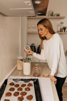 Affascinante giovane signora in piedi in cucina e cucinare i biscotti. donna allegra in piedi a casa cucina decorare cupcakes fatti in casa