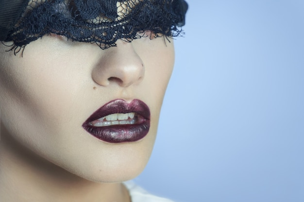 Charming young lady with black lace on eyes and beautiful lips in studio