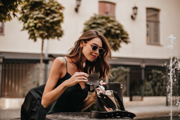 갈색 물결 모양의 머리, 트렌디한 선글라스, 녹색 실크 드레스를 입은 매력적인 젊은 여성이 도시 카페 테라스에 야외에 앉아 검은 가방을 열고 웃고 있습니다.