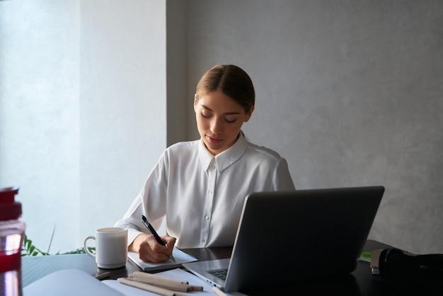 Очаровательная юная леди пишет в тетради, сидя за столом и используя беспроводной ноутбук
