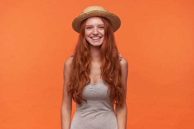 Affascinante giovane donna dai capelli londinesi in camicia grigia e cappello di paglia estivo in piedi su sfondo arancione con le mani verso il basso, guardando positivamente alla telecamera