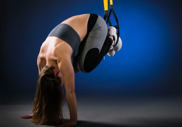 Charming young long-haired positive fitness model doing push-ups from the floor with the help of hanging straps