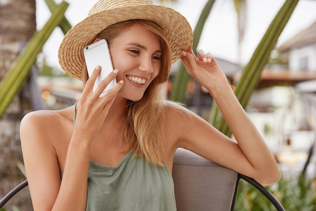 Charming young lovely woman has telephone conversation with boyfriend via smart phone, sits alone in coffee shop, wears casual clothing and summer hat, has tanned healthy skin and shining smile