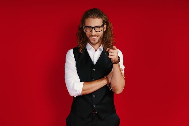 Очаровательный молодой человек в элегантной одежде смотрит в камеру и указывает на вас, стоя у красной стены