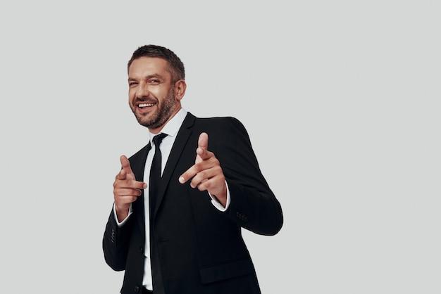 Очаровательный молодой человек в полном костюме улыбается и показывает вам, стоя на сером фоне