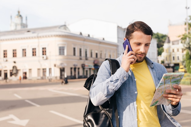 Charming young man looking at map while talking on cell phone on street