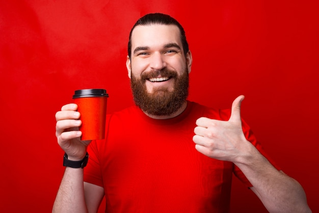 Charming young man with beard showing thumb up and holding red paper cup of coffee take away