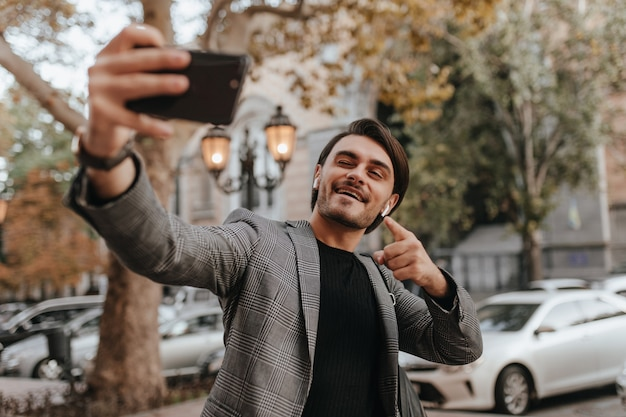 Charming young man with brunette hair and bristle, wearing dark trendy outfit, making selfie while posing on daylight autumn street