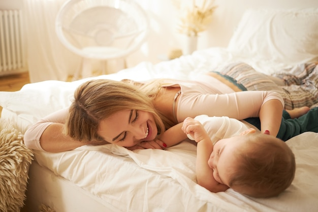 夜のスーツ姿の魅力的な若いお母さんが、かわいい赤ちゃんと一緒にベッドでくつろぎ、目覚めた後、お互いに話し、幸せな表情をしています。家族の絆、母性と乳児期の概念