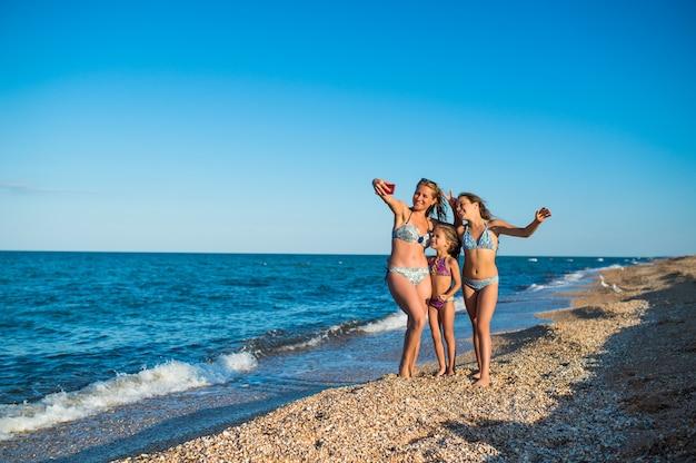 매력적인 젊은 엄마와 긍정적 인 두 딸이 바다에서 수영하는 동안 스마트 폰으로 셀카를 찍는다
