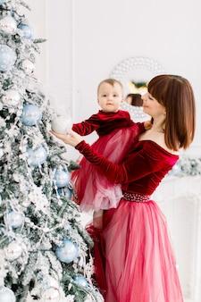 그녀의 귀여운 작은 딸을 잡고 크리스마스 트리를 장식하는 매력적인 젊은 어머니