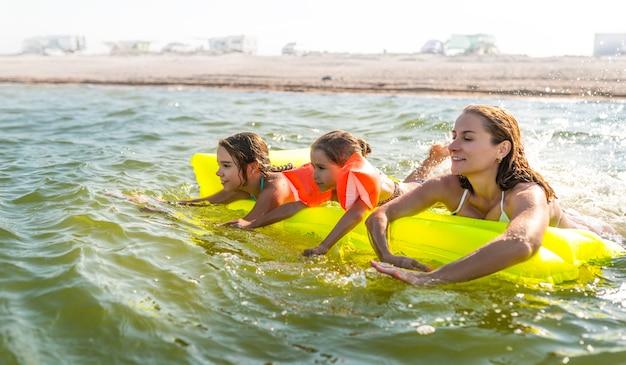 매력적인 젊은 어머니는 따뜻한 여름날에 에어 매트리스에서 호수에서 행복한 두 딸과 함께 수영하고 있습니다. 여름 휴가 개념