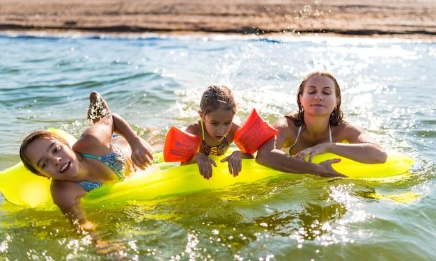 매력적인 젊은 어머니는 따뜻한 여름날에 에어 매트리스에 호수에서 그녀의 두 행복한 작은 딸과 함께 수영하고 있습니다