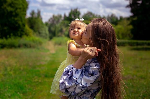 Очаровательная молодая мать целует свою маленькую дочку в зеленом парке