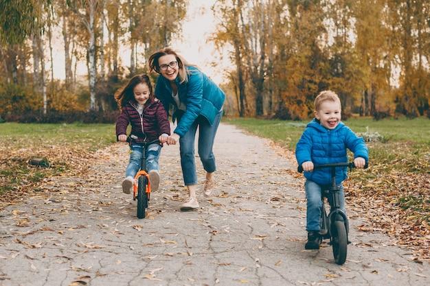 Очаровательная молодая мать играет со своей дочерью и сыном на велосипеде, пока мальчик идет. мать помогает ее маленькой девочке кататься на велосипеде.