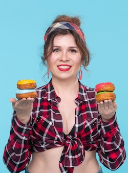 2つのドーナツを手に持ち、1つは青い背景でポーズをとっている魅力的な若いピンナップガール。コンセプトのメリットとお菓子やベーキングの販売。コピースペース