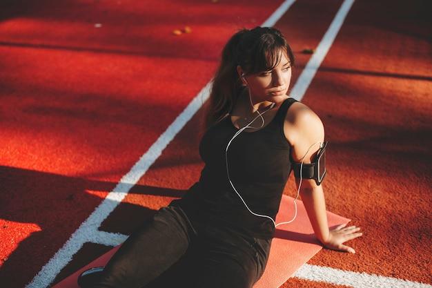 심장 하 고 스포츠 공원에서 야외 음악을 듣고 체중 감량 후 휴식 매력적인 젊은 더하기 크기 여자.