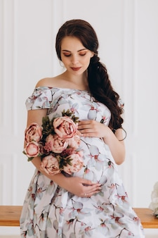 Charming young pregnant woman poses in a studio with pink flowers