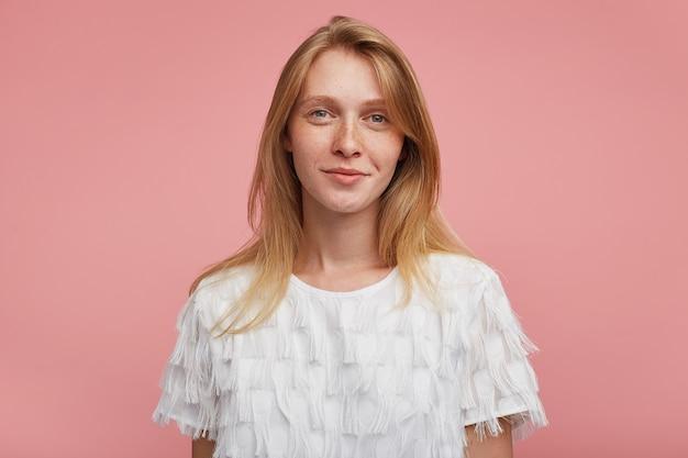 흰색 우아한 티셔츠에 분홍색 배경 위에 포즈를 취하는 동안 카메라를 긍정적으로보고 부드럽게 웃고 자연스러운 메이크업으로 매력적인 젊은 빨간 머리 여자