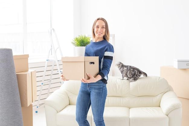 매력적인 젊은 미혼 여성이 새 아파트에 서있는 동안 움직이는 동안 물건이 담긴 상자를 들고