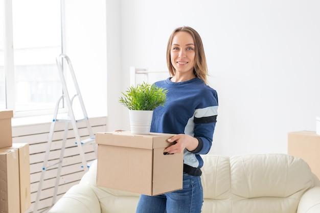 魅力的な若い独身女性は、新しいアパートに立っている間、移動しながら物が入った箱を持っています