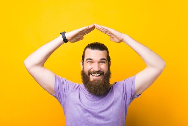 黄色の背景の上に屋根のジェスチャーを作る魅力的な若い笑顔のひげを生やした男。セキュリティと安全