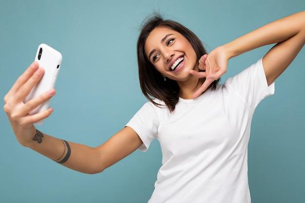 携帯電話を持って自分撮りをしている魅力的な若い笑顔の女性