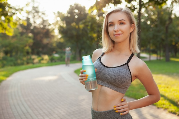 Charming young sportswoman exercising at the park in the morning