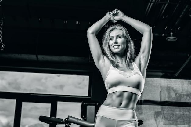 Очаровательная молодая спортсменка позирует в тренажерном зале. концепция бодибилдинга. спорт. гиревой спорт. смешанная техника
