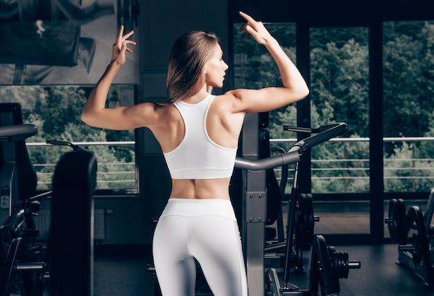 체육관에서 포즈 매력적인 젊은 sportswoman. 보디 빌딩 개념