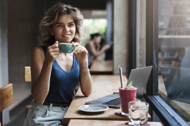 Очаровательная молодая успешная женщина-фрилансер smm-менеджер сидит за журнальным столиком, мечтательно смотрит через окно, прохожие держат чашку кофе, улыбаясь, радуются перерыву, работая ноутбуку, проводят исследования.